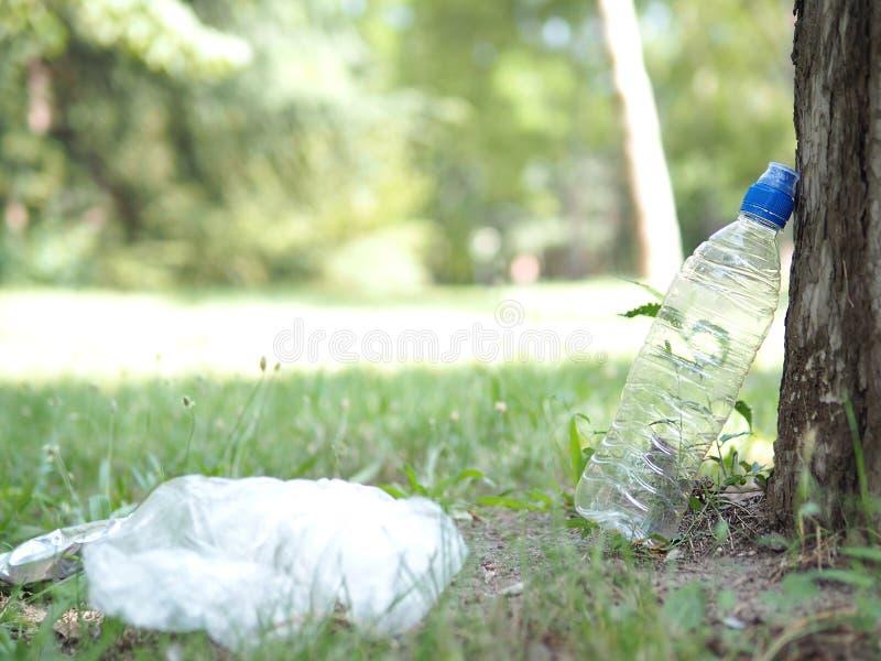 Plastikabfall, HAUSTIER-Flasche und Plastiktasche nach Waldpicknick Die Umweltverschmutzung Naturschutz stockbilder