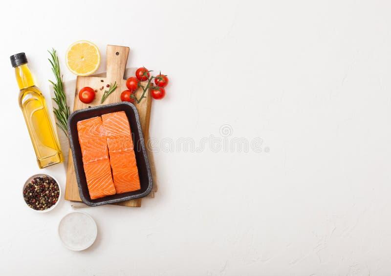 Plastikbehälter mit neuer Lachsscheibe mit Öltomaten und -zitrone auf Steinküchenhintergrund Raum für Text stockbild