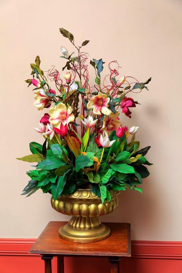 Plastikblumenanordnung im goldenen Vase stockbilder