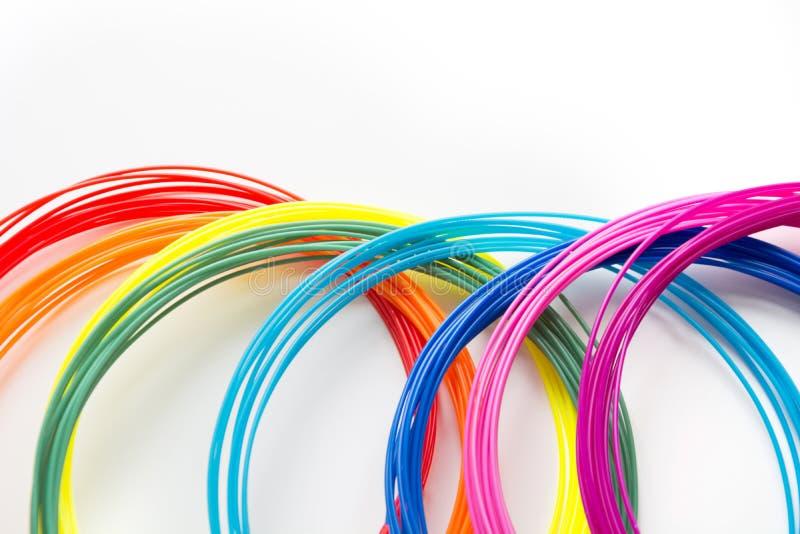 Plastikfäden des bunten Regenbogens mit für dem Stift 3D, der auf Weiß legt Neues Spielzeug für Kind stockfotos