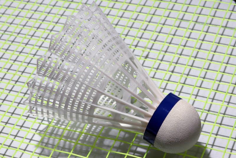 Plastikfederball von Badminton setzte an das grüne Netz des Federballschlägers lizenzfreie stockfotografie