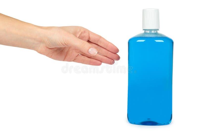 Plastikflasche mit blauer Mundwasserflüssigkeit in der Hand, lokalisiert auf weißem Hintergrund stockfoto