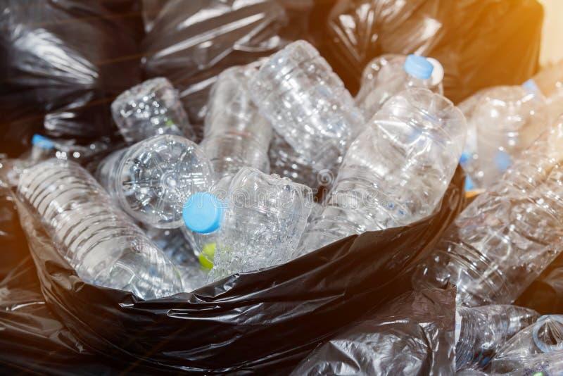 Plastikflaschen in den schwarzen Abfalltaschen, die warten genommen zu werden, um aufzubereiten stockfotografie