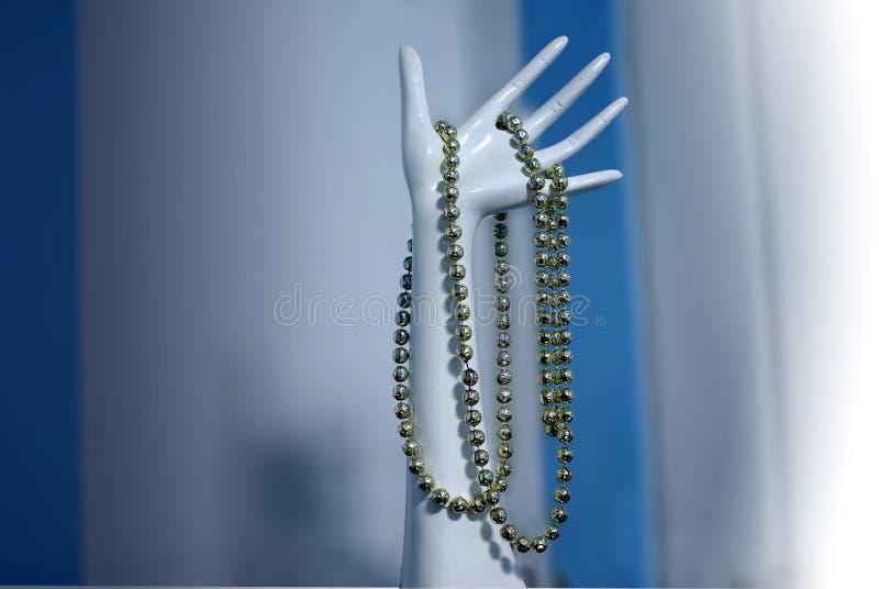 Plastikhand mit Halskette stockfotografie