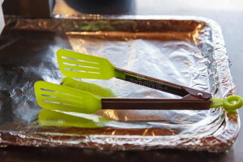 Plastiknahrungsmittelzangen auf folienumwickeltem Aluminiumbehälter für die Ernte der heißen gerösteten Bäckerei am Frühstück am  lizenzfreie stockfotografie