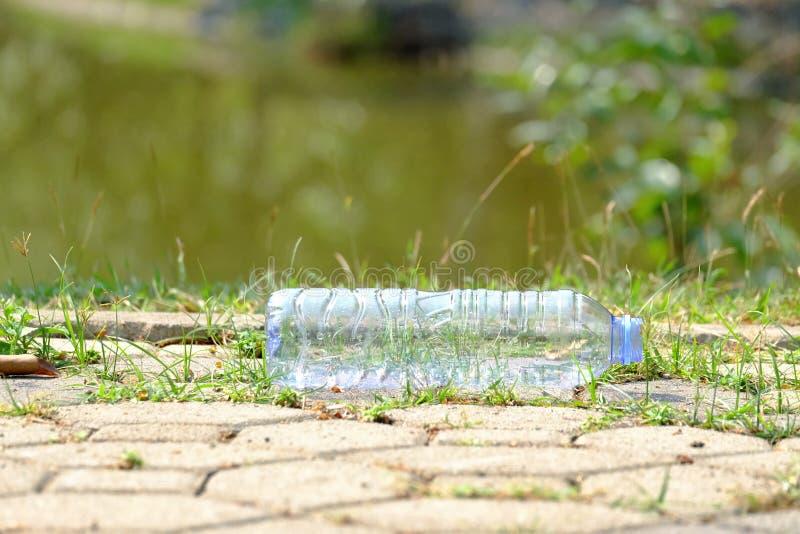 Plastikowa butelka śmieci na cementowym droga przemian przy jawnym parkiem w mieście z zielony natury i źródło wody b woda pitna zdjęcie royalty free