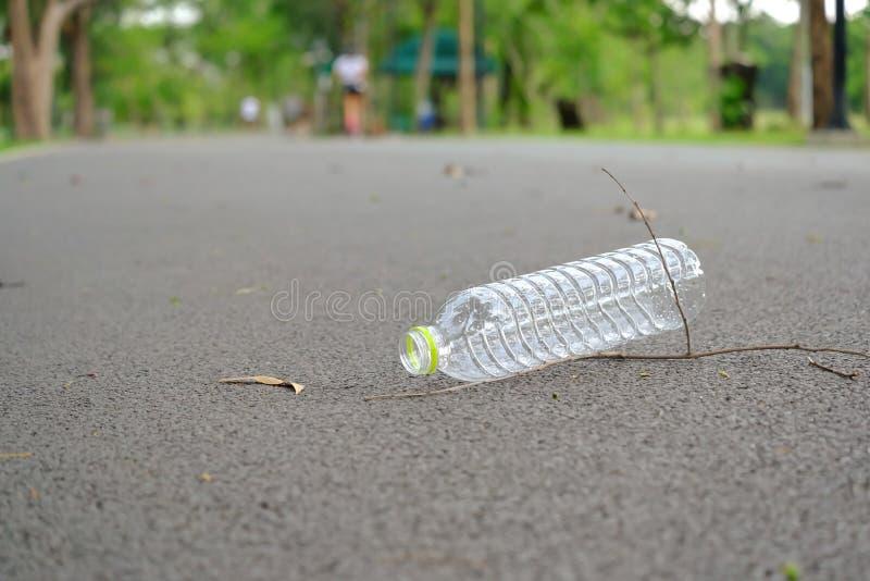 Plastikowa butelka ?mieci na drogowym parterze przy parkiem woda pitna obraz royalty free