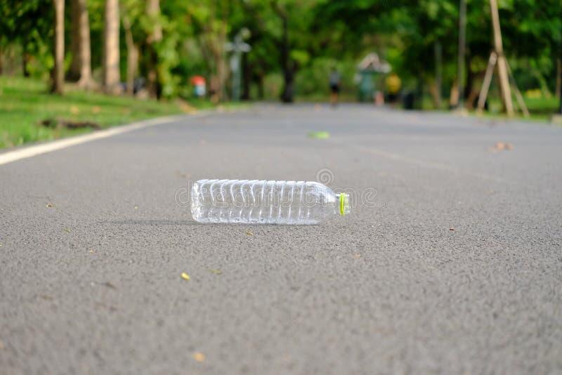 Plastikowa butelka ?mieci na ulicznym parterze przy zielonym parkiem woda pitna fotografia stock