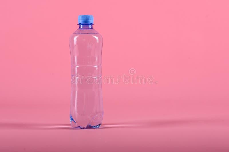 Plastikowa butelka spokojna zdrowa woda odizolowywająca na różowym tle zdjęcie royalty free