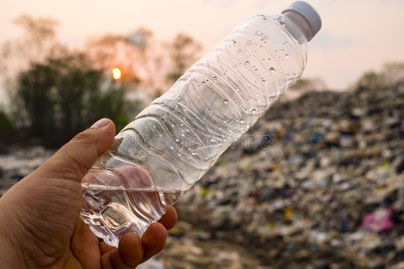 Plastikowa butelka w mężczyzna ręce na wielkim śmieci stosie, zanieczyszczeniu i obraz stock