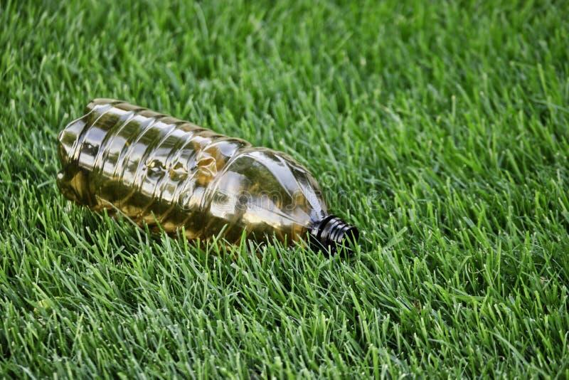Plastikowa butelka w zielonej trawie Zanieczyszczenie ?rodowiska klingerytem Ziemski ochrona dnia wizerunek Plastikowa ściółka kł obrazy stock