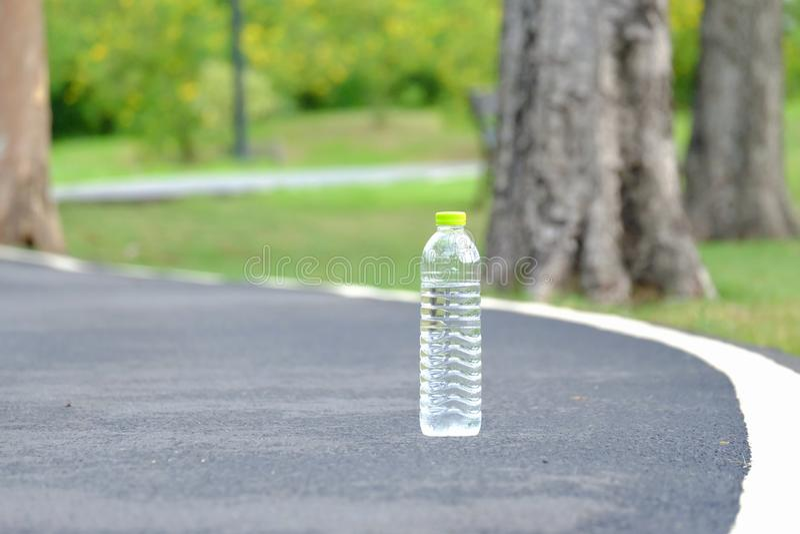 Plastikowa butelka woda pitna na bruku pas ruchu przy parkiem zdjęcia royalty free