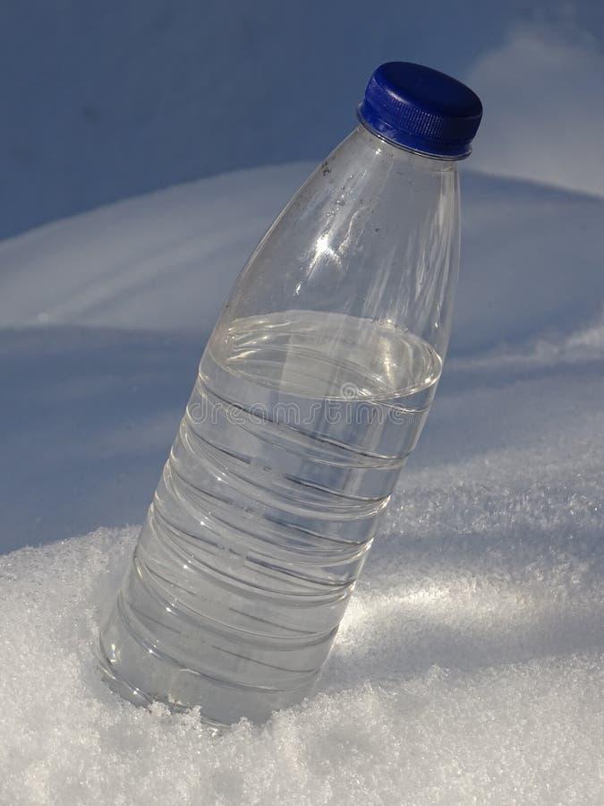 Plastikowa butelka woda w śniegu zdjęcia royalty free