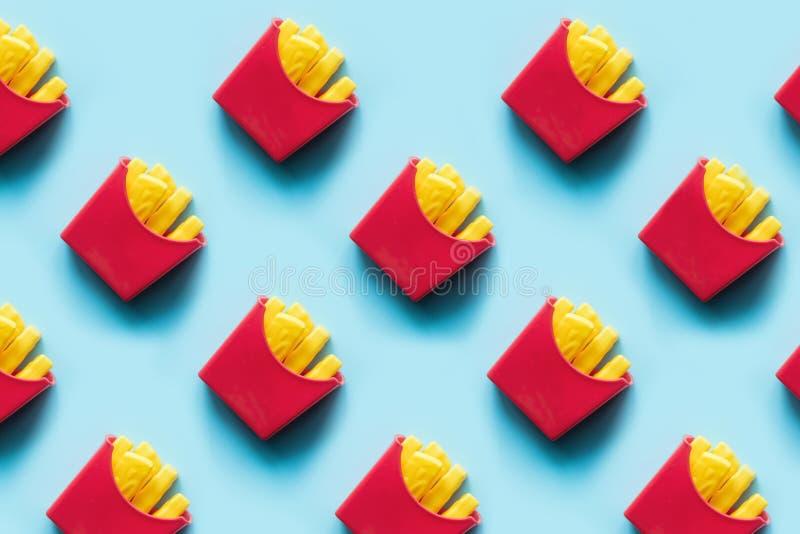 Plastikowa dziecko zabawka smażył grule dla setu z hamburgerem na błękicie Pojęcie szkodliwy sztuczny jedzenie niezdrowy Pożytecz obrazy stock