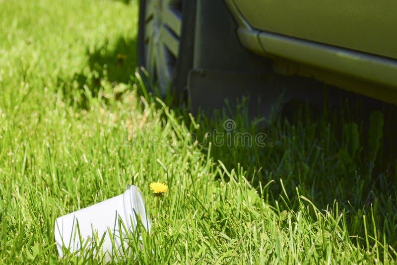 Plastikowa fili?anka w trawie Poj?cie zanieczyszczenie ?rodowiska odrzucenie plastikowi produkty u?ywa pakowa? od zdjęcie stock