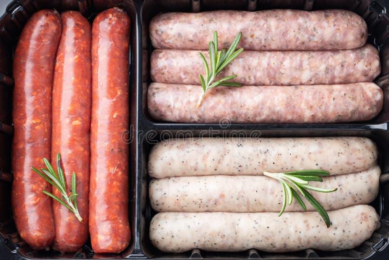 Plastikowa taca z świeżymi surowymi wieprzowiny i wołowiny kiełbasami z rozmarynami Odgórny widok fotografia stock