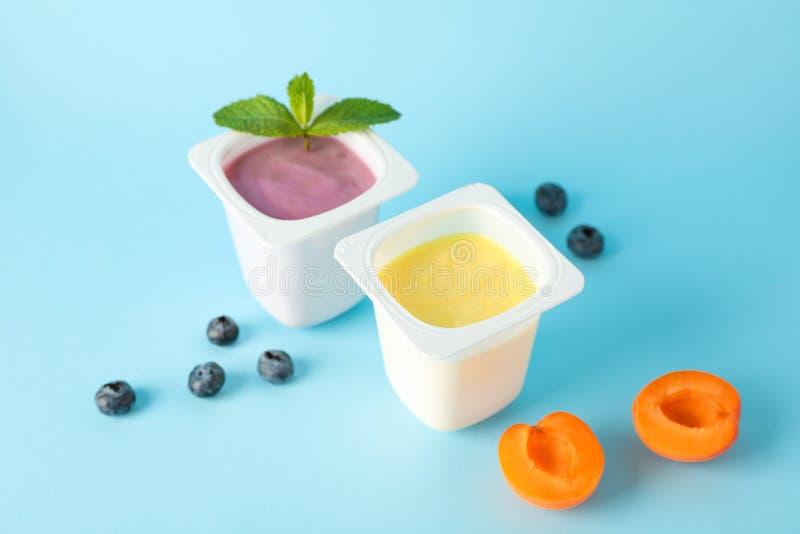 Plastikowe filiżanki z jogurtem i owoc na koloru tle zdjęcia stock
