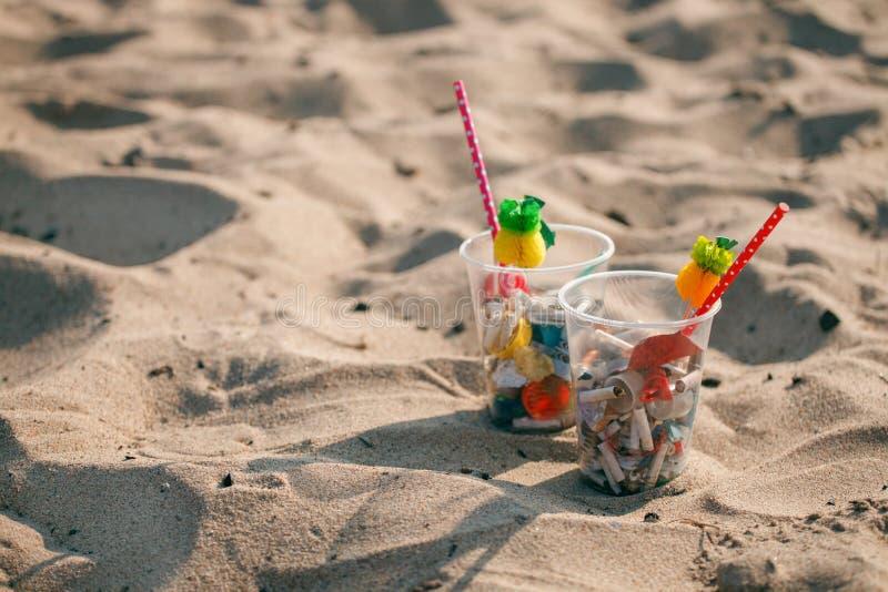 Plastikowe filiżanki z wystrojem i śmieci na plaży słomianym i tropikalnym, grat, klingeryt, butelka, piana, banialuka, sigarette obraz stock