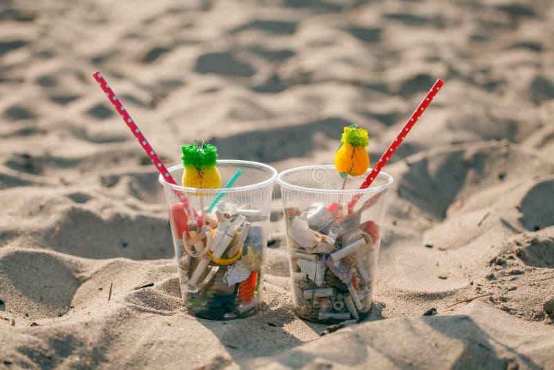 Plastikowe filiżanki z wystrojem i śmieci na plaży słomianym i tropikalnym, grat, klingeryt, butelka, piana, banialuka, sigarette zdjęcie stock