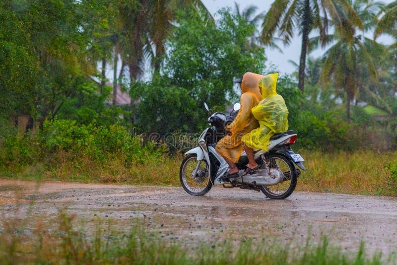 Plastikowi deszczowowie podczas gdy jadący hulajnoga w Kambodża fotografia stock