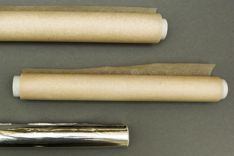Plastikowi opakunki i rolka aluminiowa folia na popielatym tle obrazy royalty free
