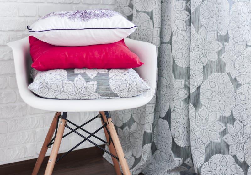 Plastikowy biały krzesło z dekoracyjnymi poduszkami na tle ściana z cegieł i zasłony zdjęcia royalty free