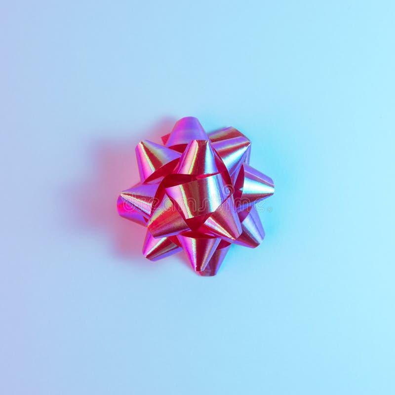 Plastikowy dekoracyjny Bożenarodzeniowy prezent ono kłania się w wibrujących śmiałych gradientowych holograficznych kolorach Boże obraz royalty free