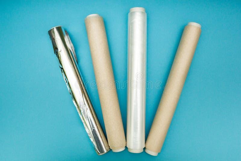 Plastikowy opakunek, aluminiowa folia i rolka pergaminowy papier na błękitnym tle, obrazy stock