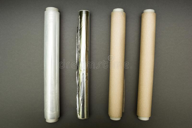 Plastikowy opakunek, aluminiowa folia i rolka pergaminowy papier na popielatym tle, obraz royalty free