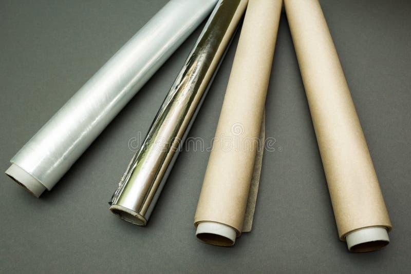 Plastikowy opakunek, aluminiowa folia i rolka pergaminowy papier na popielatym tle, zdjęcie stock