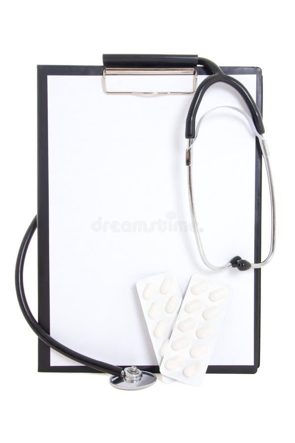 Plastikowy schowek z prześcieradłem, pastylkami i stethoscop pustego papieru, zdjęcie stock