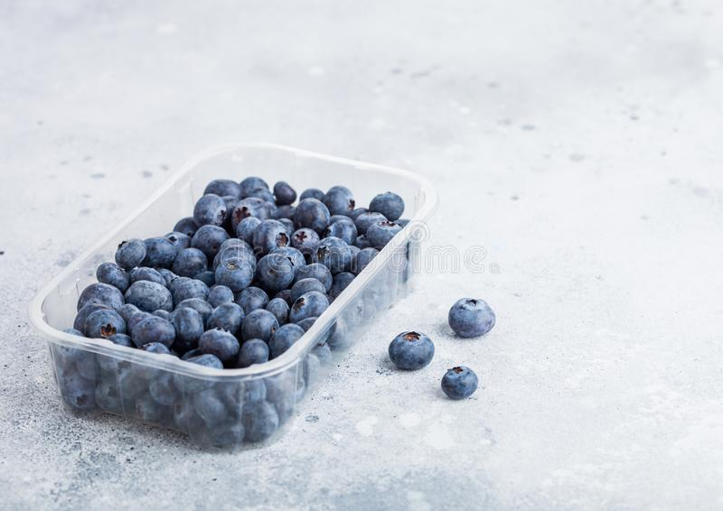 Plastikowy taca zbiornik świeże organicznie zdrowe czarne jagody na kamiennym kuchennego stołu tle Przestrzeń dla teksta zdjęcia royalty free