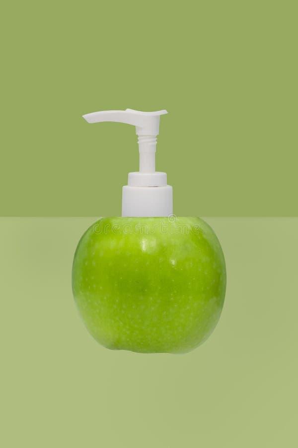 Plastikpumpflasche und Apfel auf Grün stockfoto