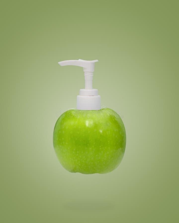 Plastikpumpflasche und Apfel auf Grün lizenzfreie stockfotografie