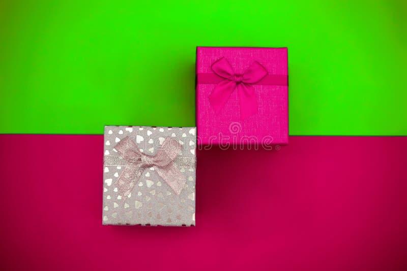 Plastikrosa und silberne Geschenkboxen auf einem Tendenzfarbhintergrund lizenzfreie stockbilder