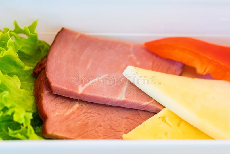 Plastikschüssel mit geschnittenem Lebensmittel für Flugzeugmahlzeitabschluß stockfotos