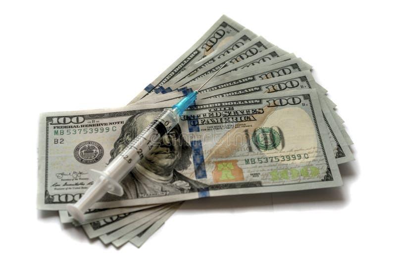 Plastikspritze mit Einspritzungslösung auf 100 Dollarscheinen Medizinisches und Geschäftskonzept Getrennt auf weißem Hintergrund lizenzfreie stockfotos