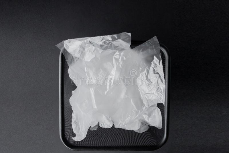 Plastiktasche mit Griffen, Handschuhe im Behälter auf einem schwarzen Hintergrund Benutzte Plastiktasche für die Wiederverwertung stockfotografie