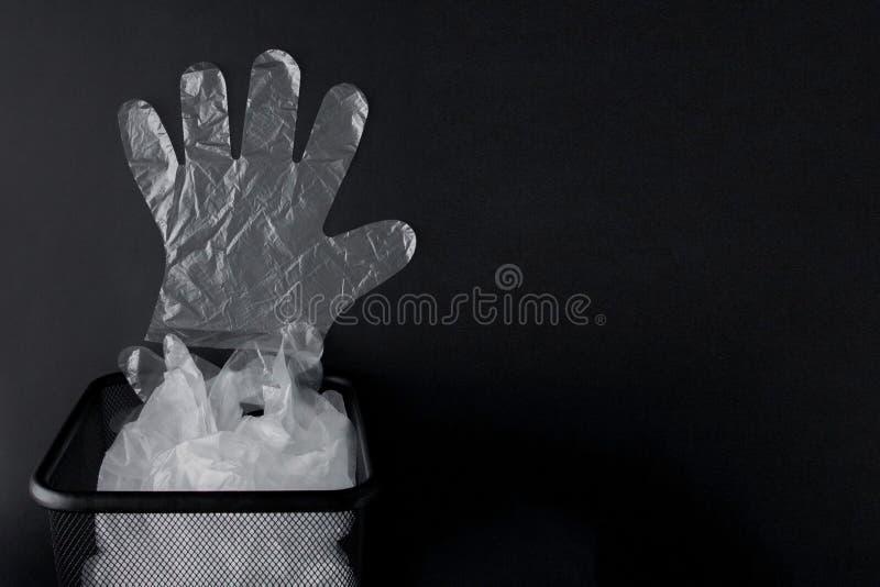Plastiktasche mit Griffen, Handschuhe im Behälter auf einem schwarzen Hintergrund Benutzte Plastiktasche für die Wiederverwertung stockbild