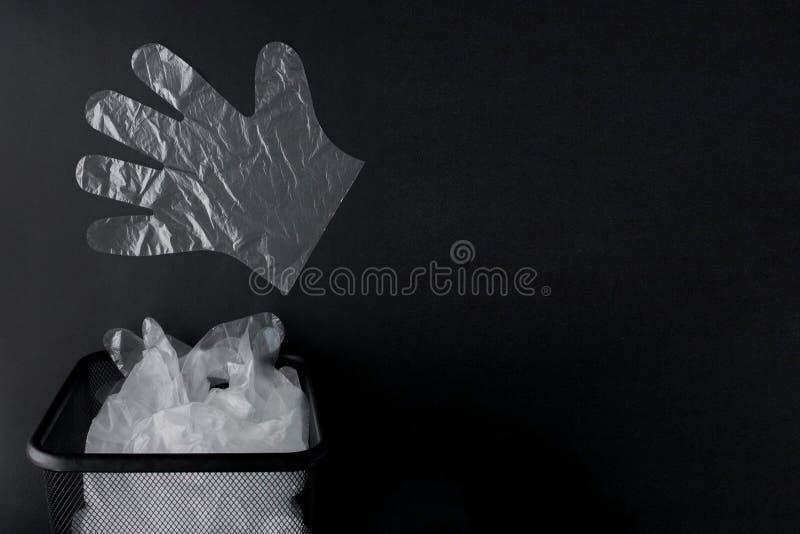 Plastiktasche mit Griffen, Handschuhe im Behälter auf einem schwarzen Hintergrund Benutzte Plastiktasche für die Wiederverwertung lizenzfreies stockbild