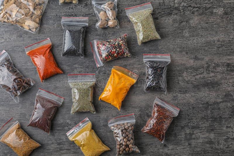 Plastiktaschen mit verschiedenen Gewürzen auf grauem Hintergrund stockbild