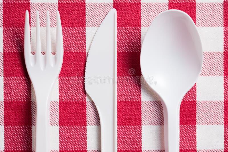 Plastiktischbesteck auf checkered Tischdecke stockfotos
