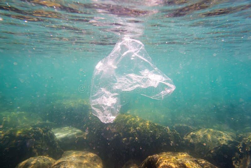 Plastikverschmutzung Fl??e einer weggeworfene Plastikabfalltasche auf einem tropischen Korallenriff, das eine Gefahr Meeresflora  lizenzfreie stockfotografie