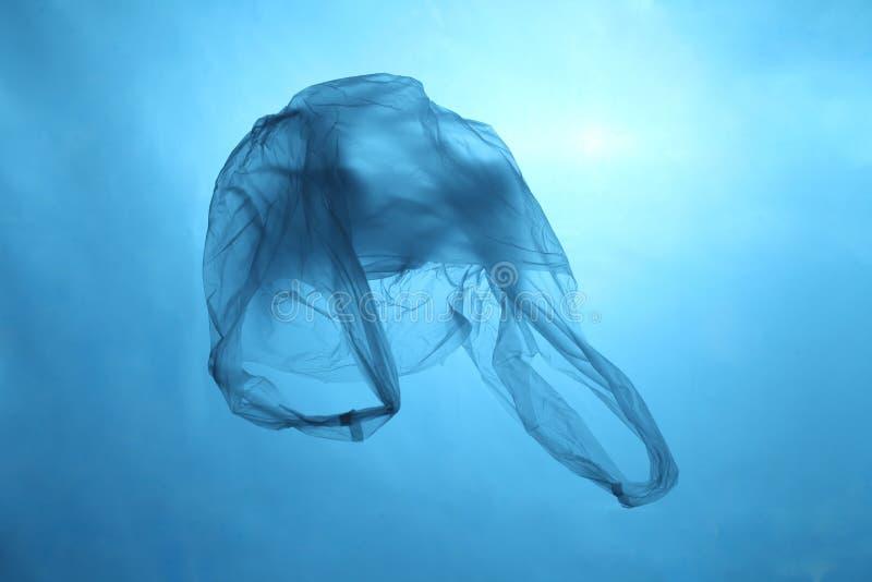 Plastp?se i bl?tt vatten, avskr?de under vatten, plast- f?rorening av haven arkivbild