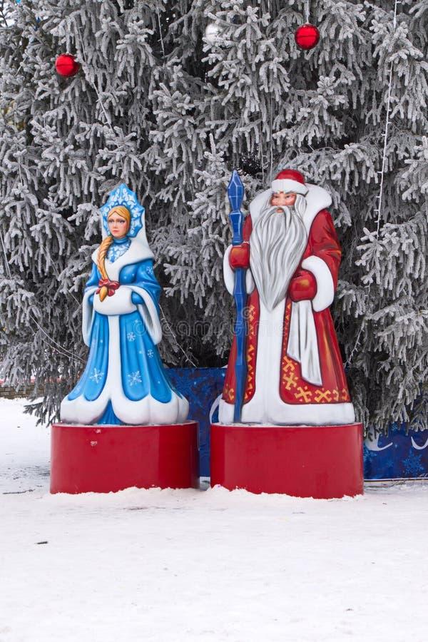 Plastsiffror från jultomten och snömajs på den fyrkantiga dekorationen för jul vid julgranen fotografering för bildbyråer