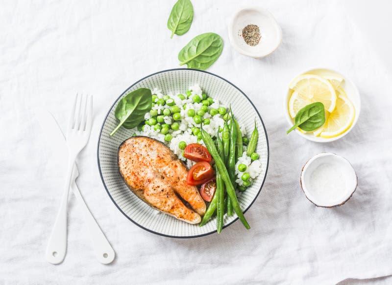 Plat équilibré sain de déjeuner de repas - saumon cuit au four avec du riz et des légumes sur un fond clair image libre de droits