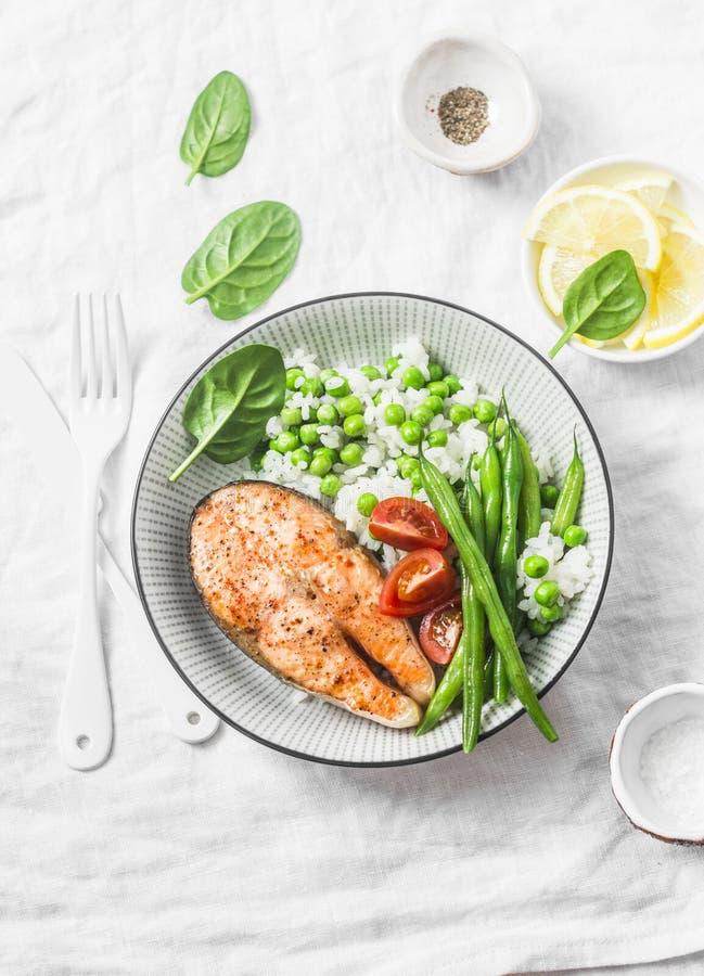 Plat équilibré sain de déjeuner de repas - saumon cuit au four avec du riz et des légumes sur un fond clair images libres de droits