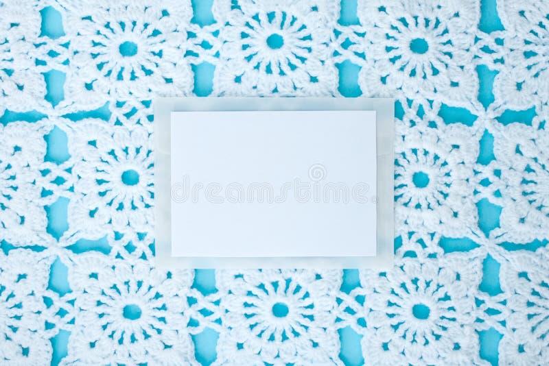Plat, étendu, une feuille de papier pour le texte sur un fond bleu avec la dentelle blanche à crochet de cru, thème d'hiver, orne photos stock