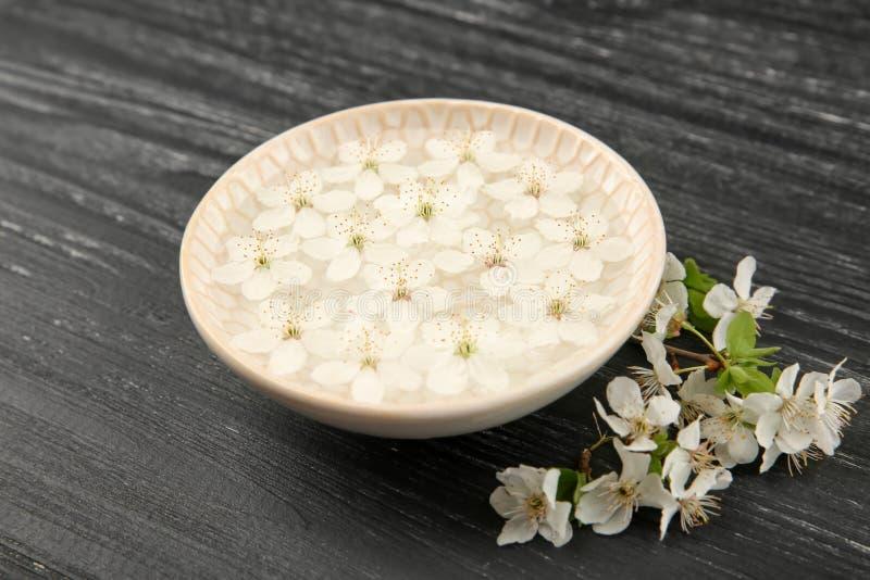 Plat avec l'eau et les fleurs de floraison sur le fond en bois foncé photo stock