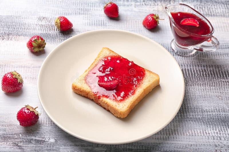 Plat avec la tranche de pain et confiture de fraise délicieuse sur la table en bois photos stock